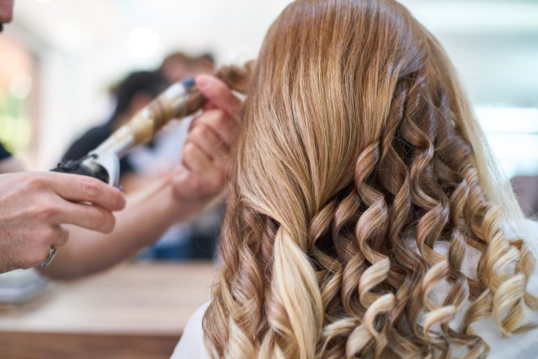 Woman hairdresser making hairstyle in beauty salon
